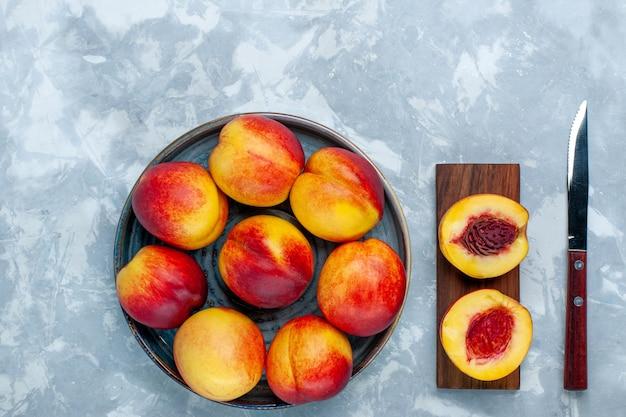 Bovenaanzicht verse perziken heerlijk zomerfruit op het lichte witte bureau Gratis Foto