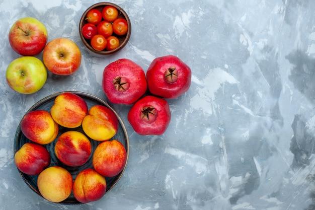 Bovenaanzicht verse perziken heerlijke zomerfruit met appels op lichtwit bureau Gratis Foto