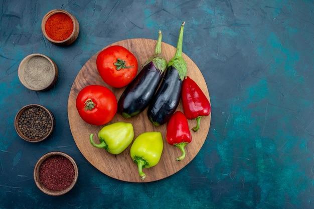 Bovenaanzicht verse rijpe groenten paprika tomaten en aubergines op donkerblauw bureau rijp plantaardig voedselmaaltijd Gratis Foto