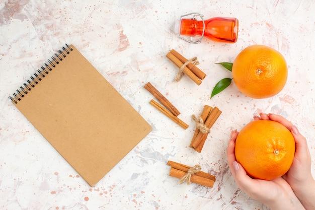 Bovenaanzicht verse sinaasappelen kaneelstokjes sinaasappel in vrouwelijke handfles een notitieboekje op helder oppervlak Gratis Foto