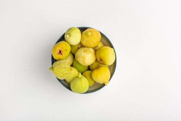 Bovenaanzicht verse vijgen zoete en heerlijke foetussen binnen plaat op het witte oppervlak Gratis Foto