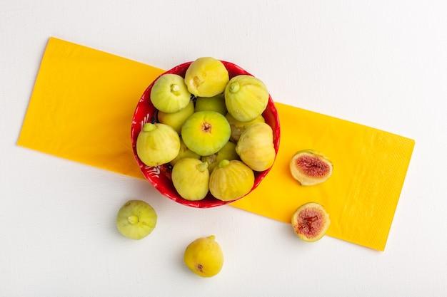 Bovenaanzicht verse vijgen zoete en heerlijke foetussen in rode plaat op wit oppervlak Gratis Foto