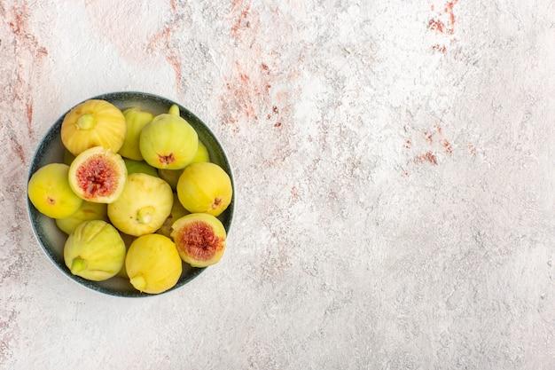 Bovenaanzicht verse vijgen zoete foetussen binnen plaat op het witte oppervlak Gratis Foto