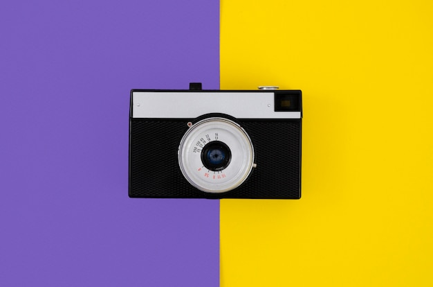 Bovenaanzicht vintage fotocamera met kleurrijke achtergrond Gratis Foto