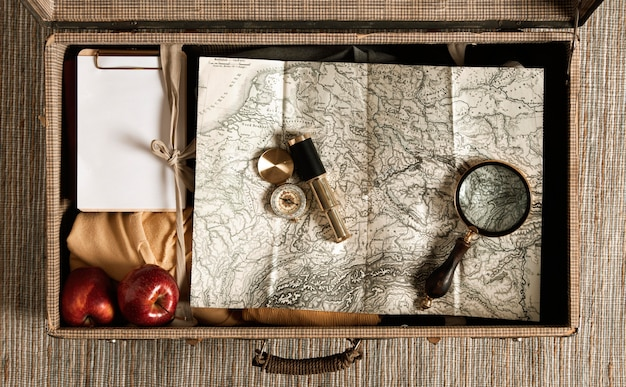 Bovenaanzicht vintage koffer met kaart en vergrootglas Gratis Foto