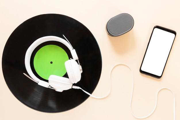 Bovenaanzicht vinyl schijf met mock-up smartphone Gratis Foto