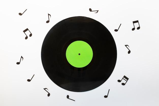 Bovenaanzicht vinyl schijf met muzieknoten Gratis Foto