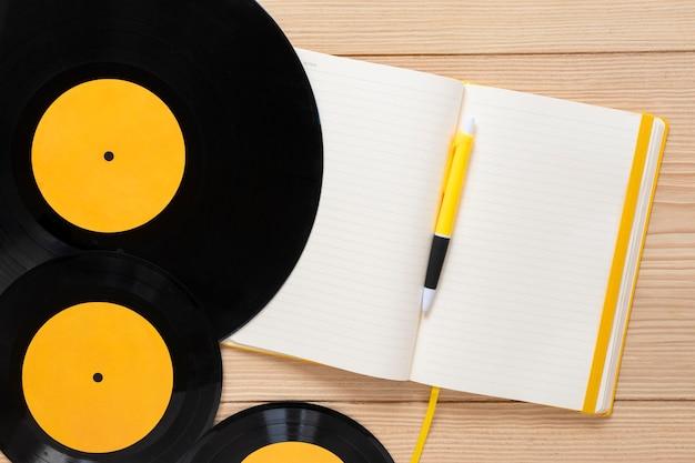 Bovenaanzicht vinylschijven met een notebook Gratis Foto