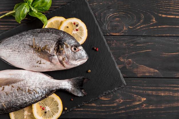 Bovenaanzicht vis en citroen op houten achtergrond Gratis Foto