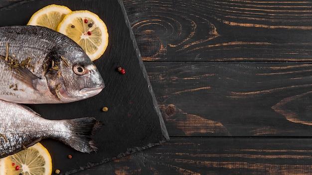 Bovenaanzicht vis en schijfjes citroen Gratis Foto