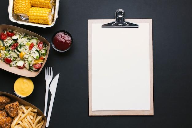 Bovenaanzicht voedsel frame met klembord Gratis Foto