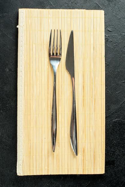Bovenaanzicht vork en mes op beige houten bord op zwarte tafel Gratis Foto