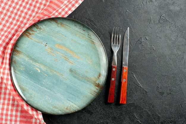 Bovenaanzicht vork en mes rood wit geruit servet ronde plaat op donkere tafel met kopie ruimte Gratis Foto