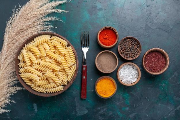 Bovenaanzicht vormde italiaanse pasta met verschillende kruiden op donkerblauwe achtergrond Gratis Foto