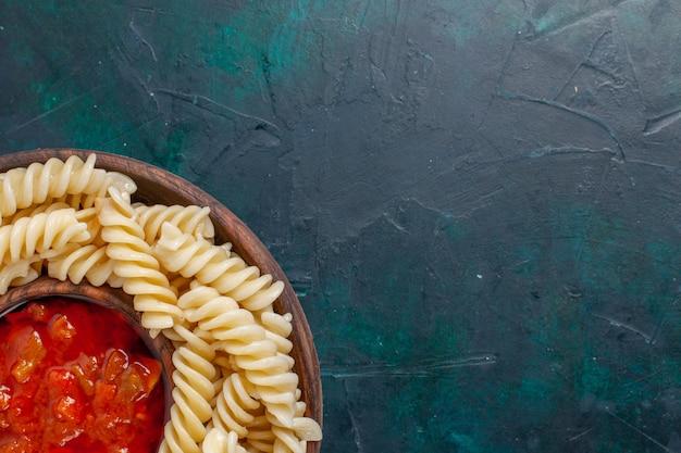 Bovenaanzicht vormige italiaanse pasta met tomatensaus op donkerblauwe ondergrond Gratis Foto