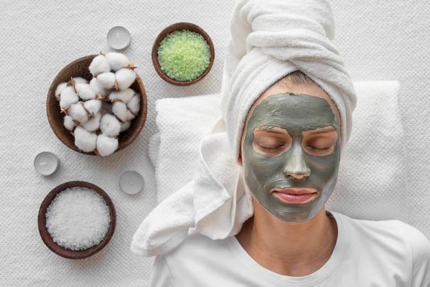 Bovenaanzicht vrouw ontspannen met gezichtsmasker Gratis Foto