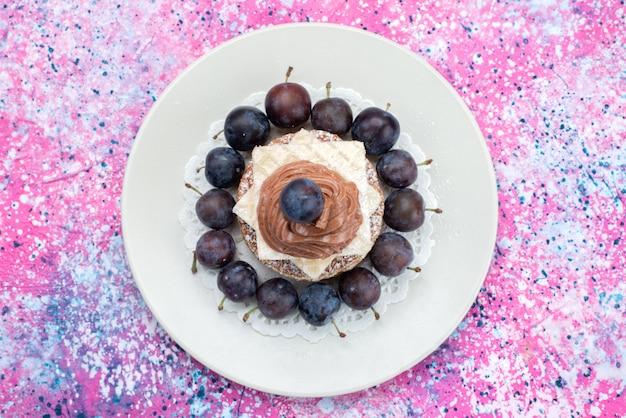 Bovenaanzicht wafel cake met room en pruimen in plaat op de gekleurde achtergrond fruit cake koekje suiker zoet Gratis Foto