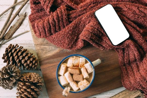 Bovenaanzicht warme chocolademelk met mock-up telefoon Gratis Foto