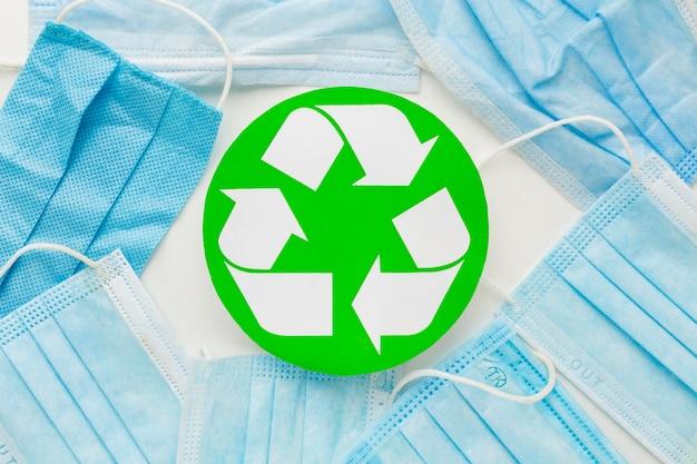 Bovenaanzicht wegwerp medische maskers en recycle symbool Gratis Foto
