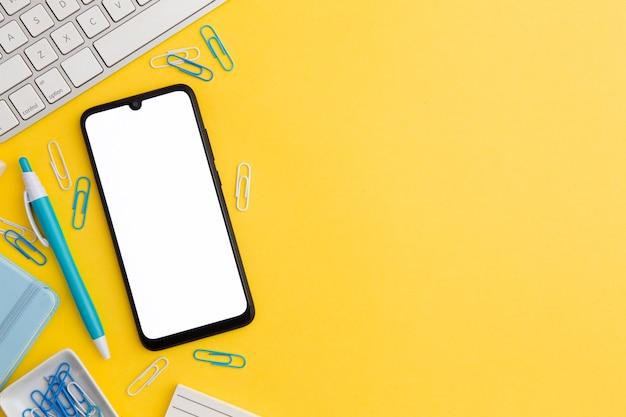Bovenaanzicht werkplek samenstelling op gele achtergrond met kopie ruimte en telefoon Gratis Foto
