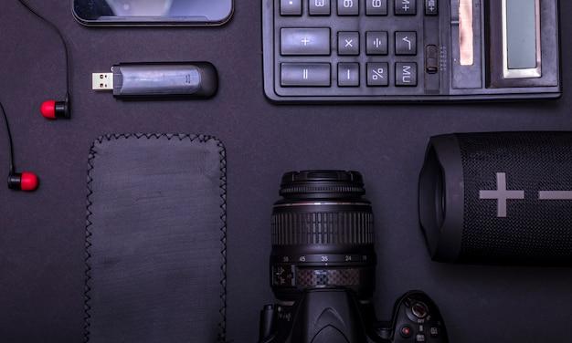 Bovenaanzicht werkruimtefotograaf met digitale camera, rekenmachine, usb-station en accessoire op zwarte tafel achtergrond met kopie ruimte. Premium Foto