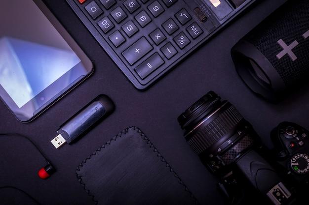 Bovenaanzicht werkruimtefotograaf met digitale camera, rekenmachine, usb-stick en accessoire op zwarte tafel achtergrond Premium Foto