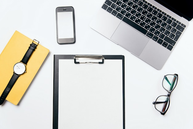 Bovenaanzicht wit bureau met laptop, telefoon, laptop, duidelijke blanco papier met vrije kopie ruimte en benodigdheden, plat lag achtergrond. Premium Foto