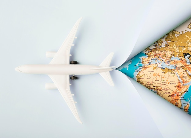 Bovenaanzicht wit speelgoedvliegtuig en kaart Gratis Foto