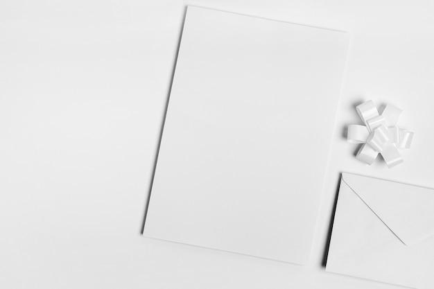 Bovenaanzicht witte envelop en boog Gratis Foto