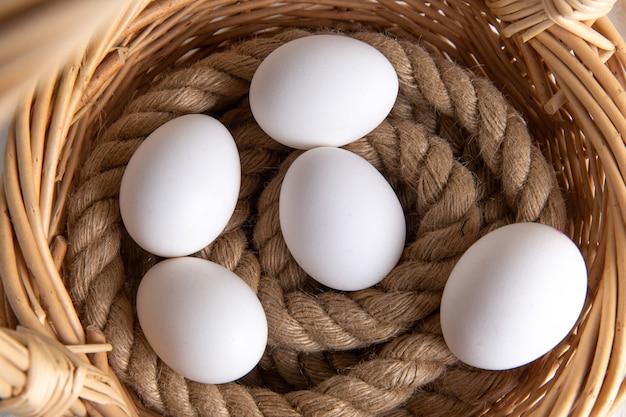 Bovenaanzicht witte hele eieren in mand op het witte bureau. Gratis Foto