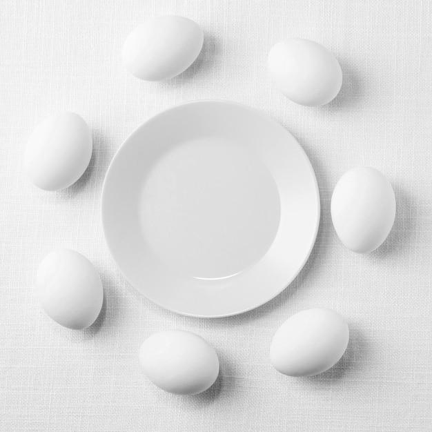Bovenaanzicht witte kippeneieren op tafel met plaat Gratis Foto