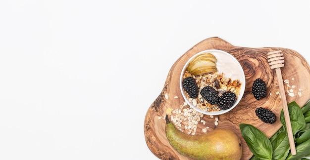 Bovenaanzicht yoghurt met haver, fruit en honing met kopie-ruimte Gratis Foto