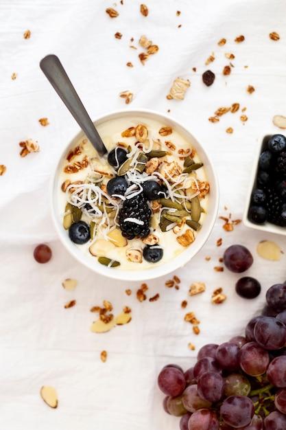 Bovenaanzicht yoghurtkom met fruit en ontbijtgranen Gratis Foto