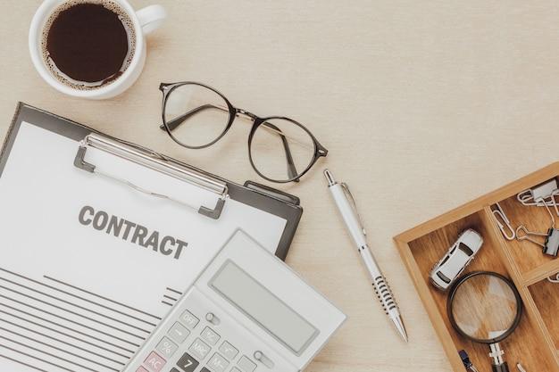 Bovenaanzicht zakelijke contractvorm met koffiebril auto calculator pen met vergrootglas op houten achtergrond. Gratis Foto