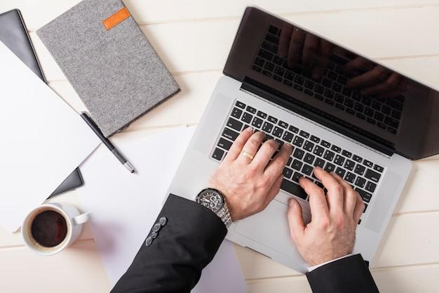 Bovenaanzicht zakenman die op laptop werkt Gratis Foto