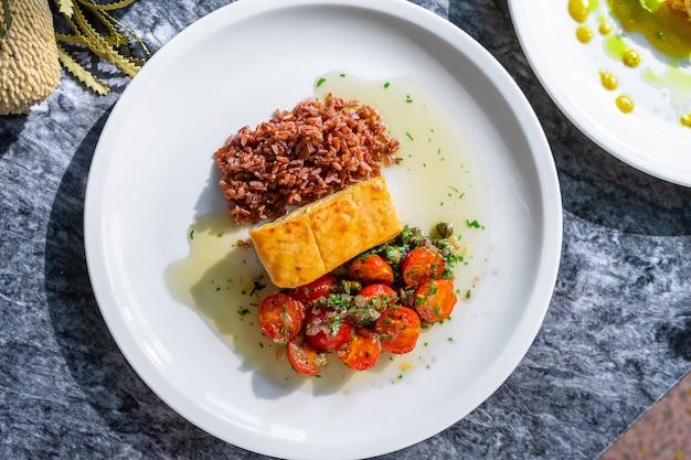 Bovenaanzicht zalm gegrilde filet met bulgur met tomaat op marmeren tafel Premium Foto