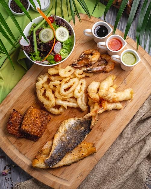 Bovenaanzicht zeevruchten voorgerechten vis inktvis garnalen met sauzen en groente salade Gratis Foto