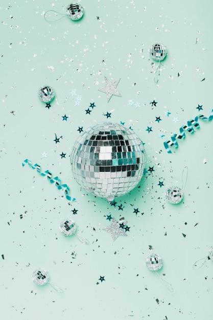 Bovenaanzicht zilveren kerstbal en blauwe achtergrond met linten Gratis Foto