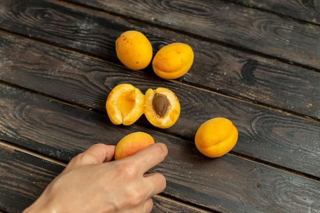 Bovenaanzicht zoete gele abrikozen zacht en vers fruit op de bruine rustieke achtergrond versheid snack Gratis Foto