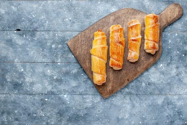 Bovenaanzicht zoete heerlijke armbanden met vulling op de grijze achtergrond zoete suiker bak gebak Gratis Foto