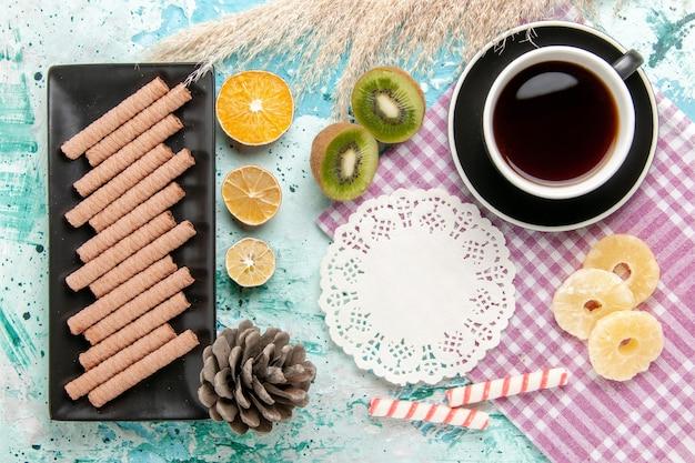 Bovenaanzicht zoete lange koekjes met kopje thee en gedroogde ananasringen op het blauwe bureau Gratis Foto