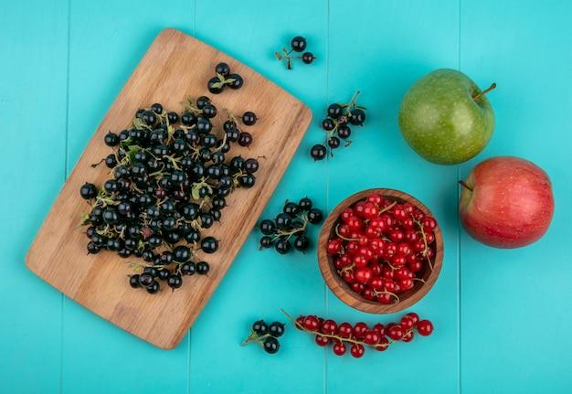 Bovenaanzicht zwarte bes op een bord met rode aalbessen in een kom en appels op een lichtblauwe achtergrond Gratis Foto