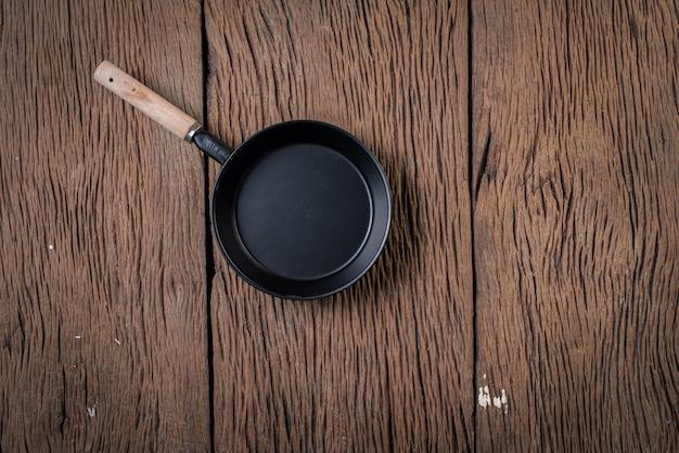 Bovenaanzicht zwarte pan op hout achtergrond Gratis Foto