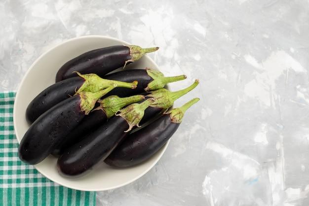 Bovenaanzicht zwarte rauwe aubergines in witte plaat op de lichte achtergrond groenten verse rauwkost maaltijd boom Gratis Foto