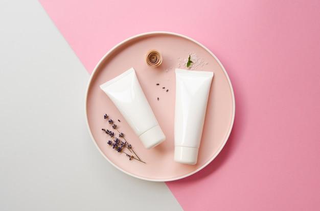 Bovenaanzichtdecoratie met crèmeflessen en bord Gratis Foto