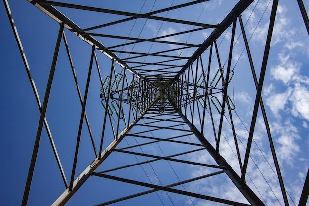Bovengrondse hoogspanningslijn onder een blauwe lucht en zonlicht Gratis Foto