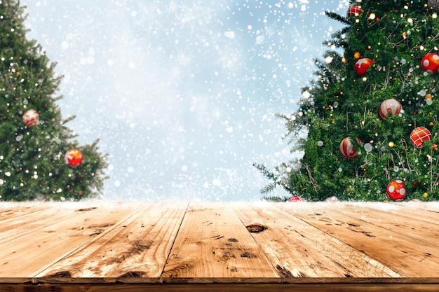 Bovenkant van lege houten lijst met mooie kerstboom en sneeuwvalachtergrond Premium Foto