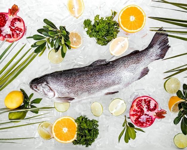 Bovenkantenmening van ruwe die vissen op ijs met vruchten wordt omringd Gratis Foto