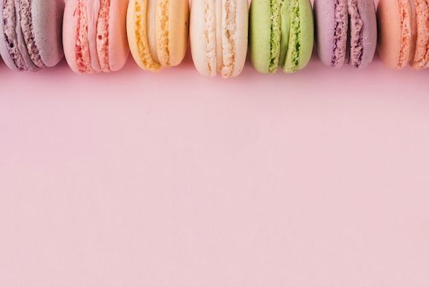 Bovenrand gemaakt met kleurrijke bitterkoekjes op roze achtergrond Gratis Foto