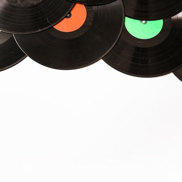 Bovenrand gemaakt met zwart vinyl record op witte achtergrond Gratis Foto